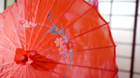 nihon : Girl hiding behind red japanese umbrella indoor. Stock Footage