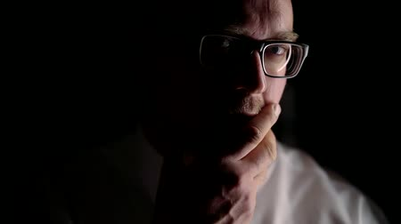 não barbeado : Portrait of sad man in dark room with hard light. Wearing a white shirt and tie on his face glasses and a little unshaven. To touch her face with his hand Stock Footage