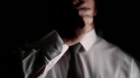 rubs : close-up of a man straightens a tie in a dark room with a hard light and rubs his hand on his face