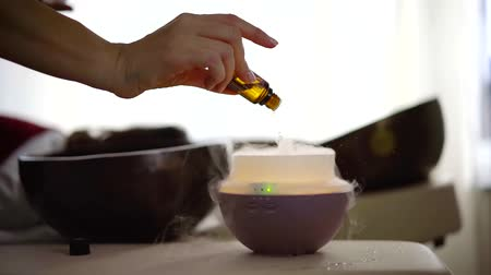 fiola : female hand is holding vial with essential oil and dropping it on aroma lamp, close-up view