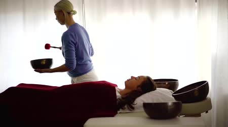 uzun ömürlü : female therapist is performing session of nada massage, striking on copper bowl over lying patient