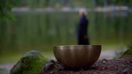 alternatif tıp : silhouette of adult woman strolling on coast of pond and copper resting bell for nada yoga Stok Video