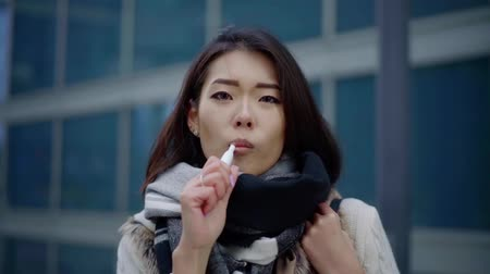 inhaling : sorrowful asian woman is smoking vape outdoors in autumn day, looking at camera, alluring girl
