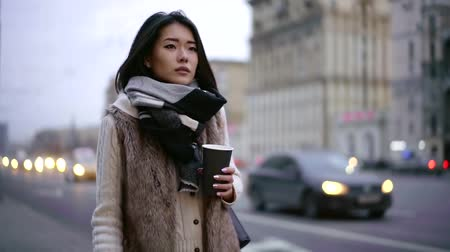 urbanística : lonely unhappy asian woman is walking along road in city in evening time, holding paper cup