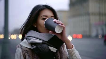 urbanística : charming lonely asian girl is strolling in city in twilight, drinking coffee from paper cup