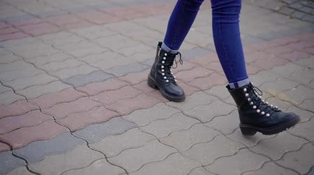 drawstring : feet of teenage girl close-up view, stepping over ground outdoors in city in fall day, walking alone