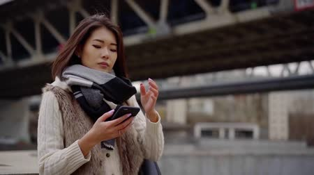 использование : pretty asian girl is browsing by mobile phone with wireless internet, standing outdoors in city