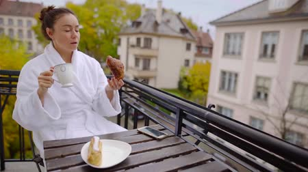 taras : woman is having breakfast on a balcony of apartment, biting croissant and drinking coffee