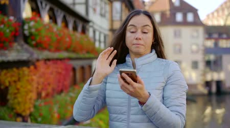 half timbered : charming brunette is typing and sending messages by smartphone in small city with houses in background