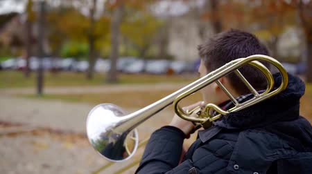 trumpet : alone male musician is sitting on a bench in park in autumn day and playing trumpet