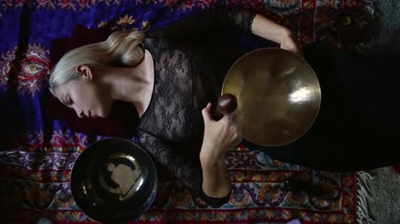 ascetic : woman is relaxing lying on a floor, holding singing copper bowl on her belly and rotating stick-resonator