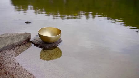 tibeti : traditional indian copper bowl for nada therapy is lying on stone in water of lake in forest Stock mozgókép