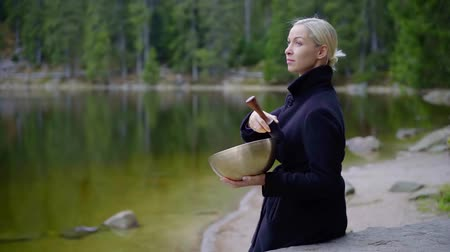 tibeti : blonde woman is sitting on a shore of calm lake in forest and making sounds by copper bowl Stock mozgókép