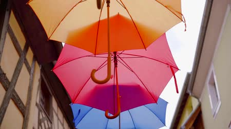 suspensão : different colors umbrellas are suspended over street in small city, tilt up view