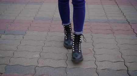 drawstring : slim female legs are stepping on paving path in city street in autumn day, close-up view Stock Footage