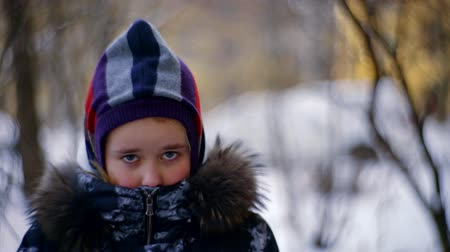 marad : Close up. Portrait of a baby girl in warm winter clothes. Standing in the street and trying to stay warm. Beautiful blurred background.