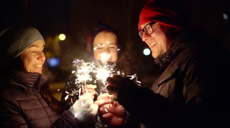 christmas party : happy happy family celebrate the new year with Bengali candles standing on the street in the winter night Stock Footage