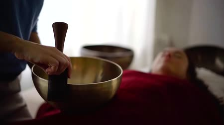 uzun ömürlü : close-up view of hands moving stick-resonator around of singing bowl during nada yoga session Stok Video