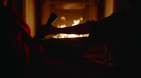 lényeg : silhouette of hands of tibetan monk touching resting bell by stick-resonator in room with fireplace Stock mozgókép