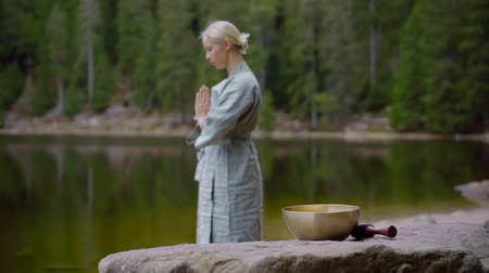 alternatif tıp : blonde caucasian woman is praying on shore of forest lake in tibet, making meditation practice