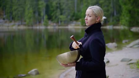 lényeg : female specialist is working with singing bowl on a coast of lake in woodland in autumn day Stock mozgókép