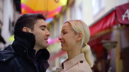 evli : blonde woman is hugging with her husband on small city street, he is kissing her cheek Stok Video