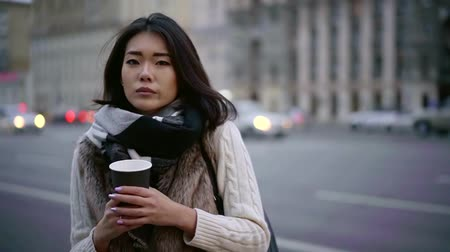 urbanística : sad chinese woman is standing alone on city street in cold weather, holding cup of coffee Vídeos