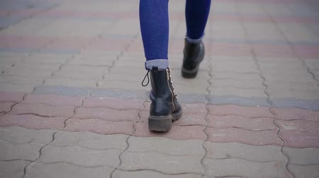 cipőfűző : woman is walking in city in daytime in autumn, close-up view of her shoes from back, strolling