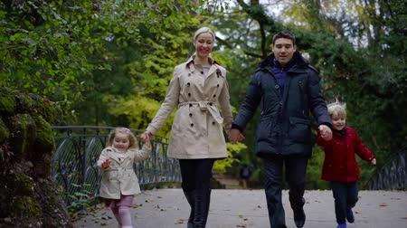čtyři lidé : happy caucasian family is running together in park, parents is holding hands of little kids Dostupné videozáznamy