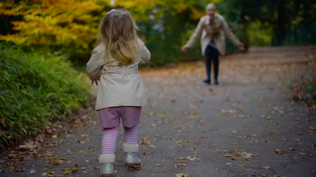 przedszkolak : funny little girl is running to her mother over pedestrian path in park in autumn day