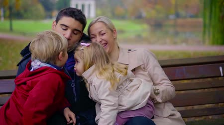 their : little sister and brother are kissing sitting on laps of their parents, having fun and spending time joint family Stock Footage