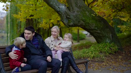 their : happy man is resting in park with his family, his wife is sitting on bench and holding daughter