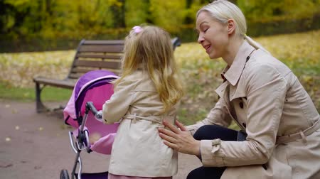 мама : cute little girl is kissing her mother in park area in city in autumn day, happy childhood Стоковые видеозаписи
