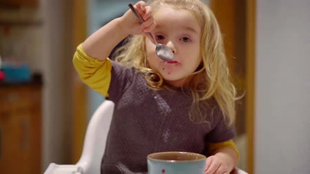 zabkása : blonde charming little girl is eating berries by spoon from big bowl in home, independent child