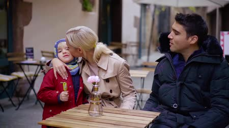 rodič : happy parents are sitting at table on open air terrace of cafe, woman is kissing little son