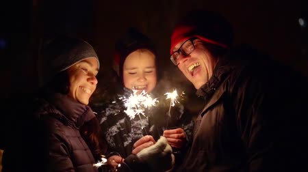 bengali : cheerful family celebrating new years eve on the street in the cold. burning candles sparkle in your hands Stock Footage