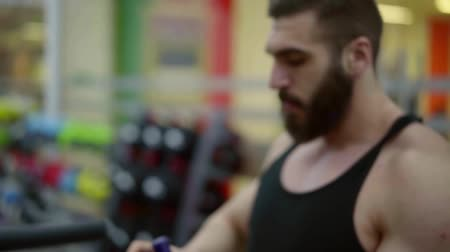 diluted : bearded muscular male bodybuilder drinks amino acid complex after performing exercises on the bars