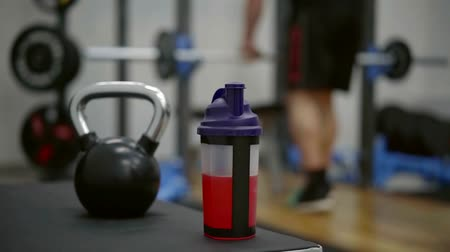 balanced : male athlete performed the exercise and went to pick up a shaker with water-diluted amino acids for rapid recovery of damaged muscles Stock Footage