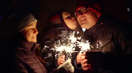 bengali : successful happy family celebrates Christmas in the yard in winter with sparklers in their hands