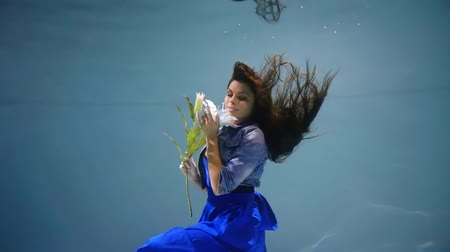 young girl in a blue dress under water with a flower in her hand like in a fairy tale