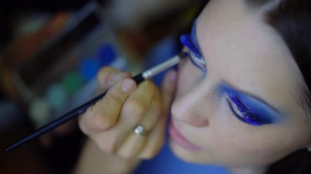 close up. the face of a young girl. hand wizard causes a vivid makeup color for blue eyes with beauty of your eyelashes