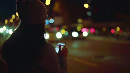 Midnight girl uses smartphone stands outside in autumn, near the road and uses smartphone. Tap the touch screen and enter text. She surfs the Internet.