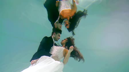 wedding ceremony under water the couple hugging in the pool Stock mozgókép