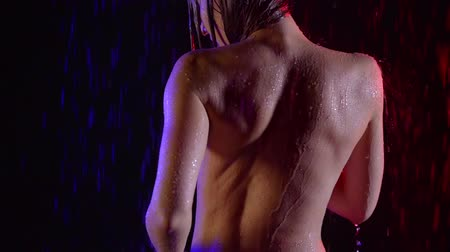 back of a slender athletic young girl. washes under the shower in a dark room in the light of neon red and blue Stock mozgókép