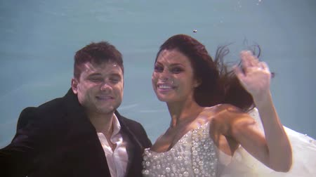 cute couple at a wedding underwater waving their hands greeting with smiles at the camera