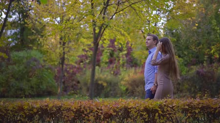 young couple model in love, Autumn Park nature couple man and woman walking in the Park couple holding hands, happy couple slow motion