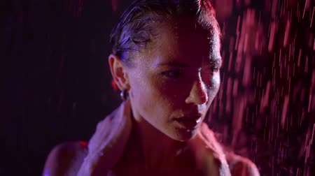 kıvırcık saçlar : Portrait of a cute sad girl looking at the rain in the shower with wet hair. drops of water fall on her face. Slow motion Stok Video