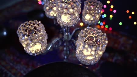 Close-up shot of crystal lamp, blurred christmas lights on background and singing bowl with water in it.