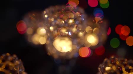 Defocused sparkling lamp and lots of colorful lights on a background in a dark room.