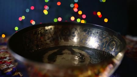 Close-up shooting of a tibetan bowl with ornaments half full of water on the table.